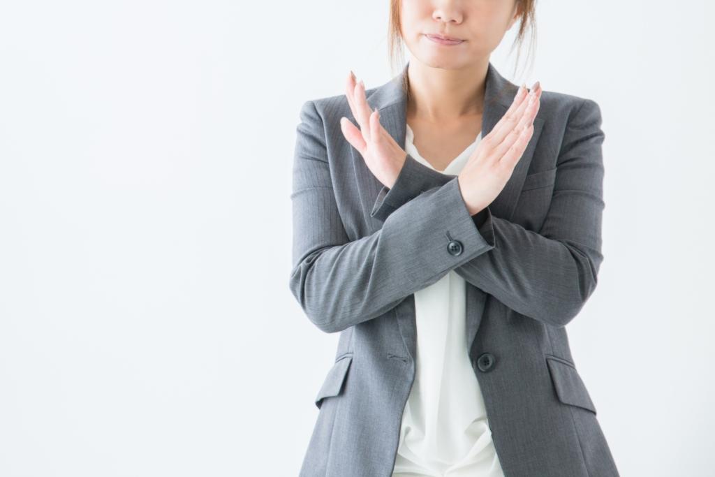 手でバツを表現している女性